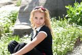 blond girl sitting in the garden poster