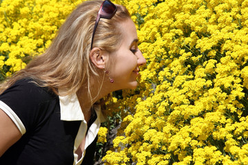blond girl smelling yellow flowers
