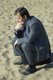businessman deep in thought on the sand poster