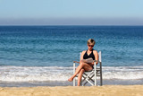 woman relaxing on a beach with a book poster