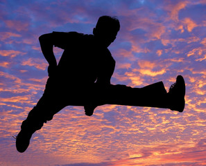 boy jumping high in the air against the sunset