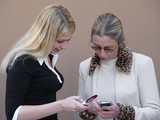 two blond women discussing their cell phones poster