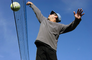 man hitting the ball over the net