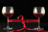two wine glasses wrapped with a red tape poster