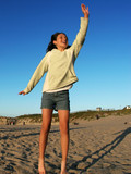 happy girl jumping on the beach poster