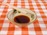 soy sauce and chopsticks on a home table poster