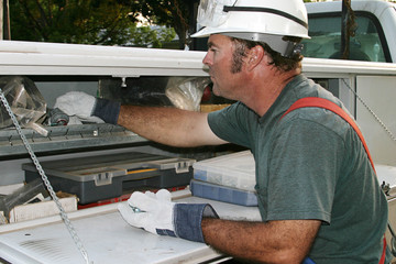 electrician reaches in service truck