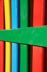 colourful rows of painted wood on a playground fence