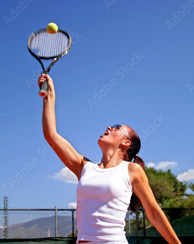 female tennis player reaching to hit ball with deep blue sunny s