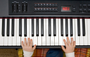 young boys hands on an electronic piano or keyboard