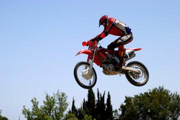 moto x or motor cross bike leaping through the air on a hot sunn