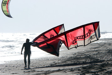 kitesurfer walking along the sandy beach at the end of a busy da