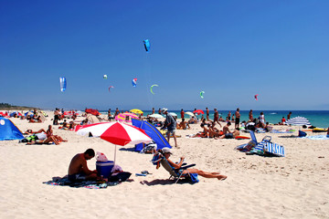 white, sunny, sandy beach full of kitesurfers in tarifa, spain