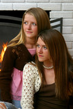 pretty sisters by fireplace poster