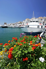 flowers and boat in puerto banus port in spain