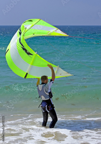 young male kitesurfer holding kite steady