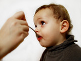 baby with a spoon in a mouth poster