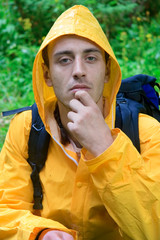 backpacker in a yellow coat resting