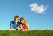 couple lies on meadow with cloud