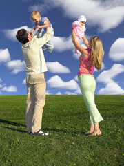 happy family with two children on blue sky with cl