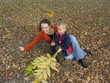 mother with son with and on autumn leaves