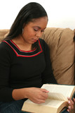 woman reading book on couch poster