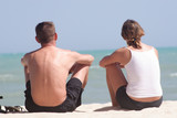 adult couple sitting on the beach poster