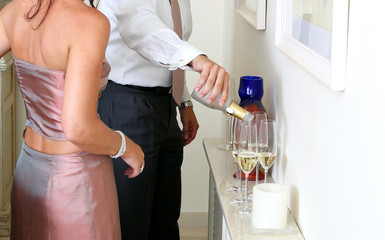 man pouring champagne at a dinner party