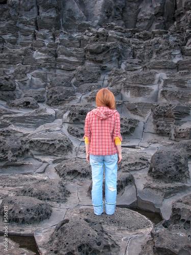 woman standing on volcanic rock