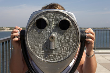 woman looking through a coin operated binoculars