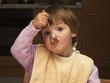 kind beim essen mit löffel im mund