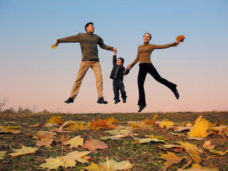 fly happy family with autumn leaves. color sunset