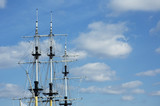 masts of frigate over blue sky with space for text poster