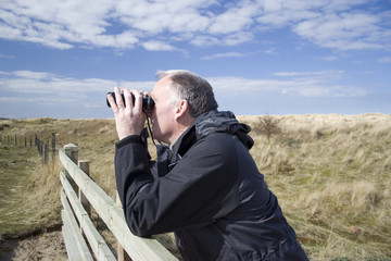 man birdwatching through binoculars