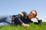 man lying on grass poster