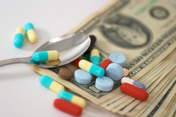 pills on money with spoon, shallow depth of  field