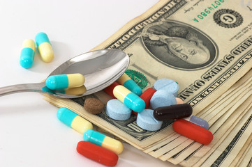 assorted pills with money with spoon