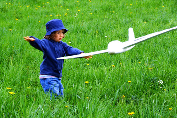 girl with airplane on the grass
