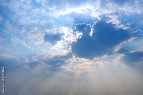 poster of sun rays from under cloud covering the sun blue sky background