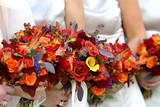 red and orange flower bouquet on a wedding dress. poster
