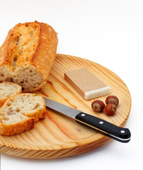 pate, bread, hazelnuts and knife on wood plate