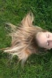 blond woman lying on grass poster