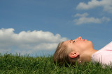 young woman lying on grass poster