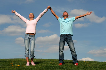 couple standing on grass with raised arms