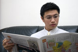 young asian entrepreneur reading newspaper poster