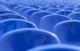 rows of empty blue chairs poster