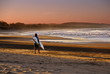 surfer goes to the beach at sunset
