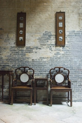 chinese chairs by brick wall