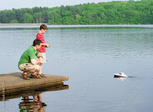 father and son playing with a boat