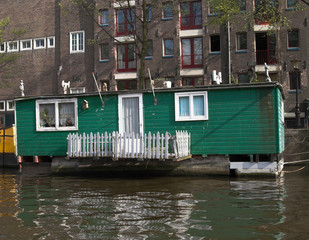 green houseboat in city canal, amsterdam, netherlands